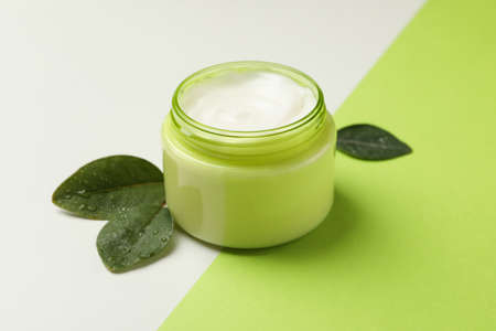 Jar of cosmetic cream and leaves on two tone background