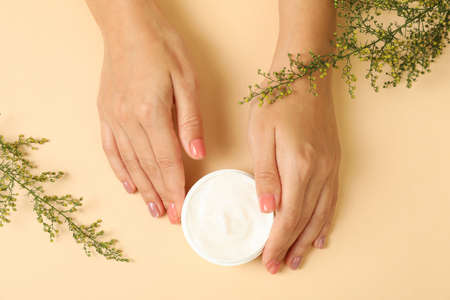 Female hands hold jar of cosmetic cream on beige background 免版税图像