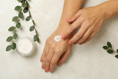 Female hands with cosmetics cream on white background