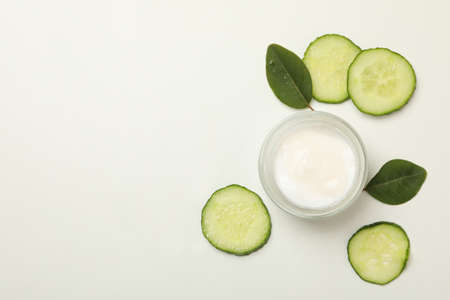 Jar of cosmetic cream and cucumber slices on white background 免版税图像