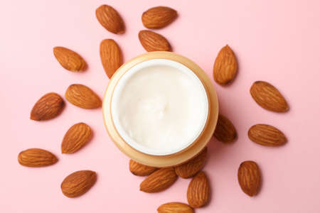 Jar of cosmetic cream and almond on pink background