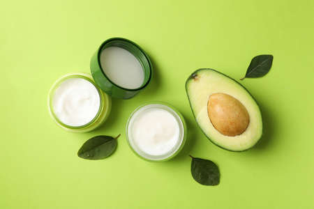 Jars of cosmetic cream, leaves and avocado on green background