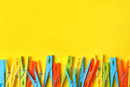 Clothespins on yellow background, space for text 版權商用圖片