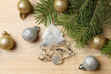 Pine branches and Christmas baubles on wooden background
