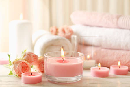 Pink scented candles on white wooden background Imagens