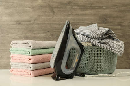 Iron, basket with laundry and pile of towel against wooden background