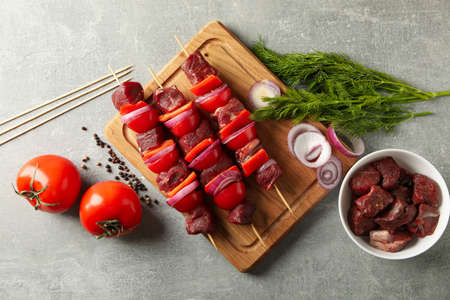 Board with raw shish kebab and ingredients on gray background