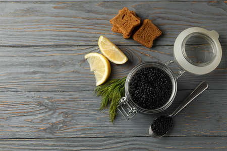 Jar with black caviar, bread, dill and lemon on wooden background, space for text Banco de Imagens