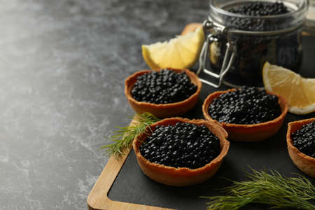 Board with tartlets and jar with caviar on black smokey background, space for text