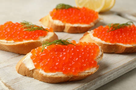 Wooden board with sandwiches with red caviar, close up