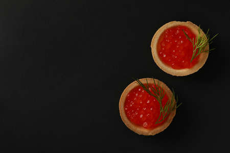 Tartlets with caviar on black background, space for text Banco de Imagens