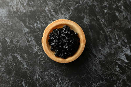 Tartlet with caviar on black smokey background, top view