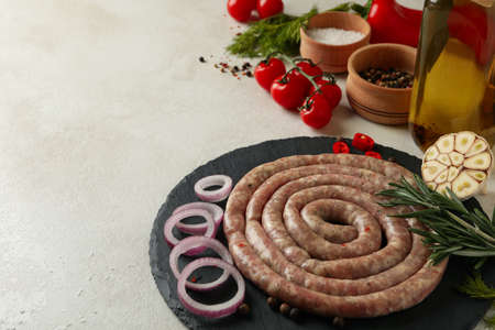 Tray with raw sausage and ingredients on white textured background