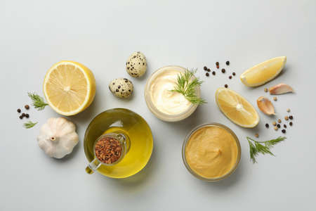 Bowl with mayonnaise and ingredients for cooking on white background, top view