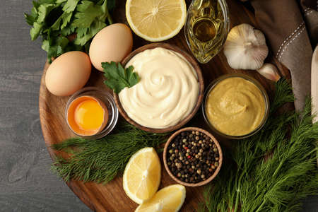 Board with bowl of mayonnaise and ingredients for cooking on dark wooden background