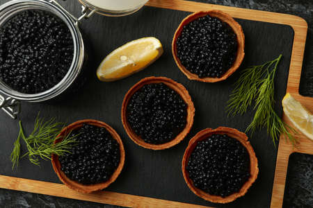 Board with tartlets and jar with caviar on black smokey background, top view Banco de Imagens