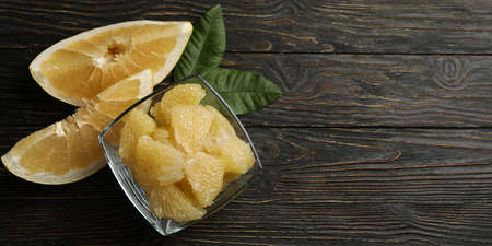 Bowl with pomelo fruit slices and leaves on wooden background Banco de Imagens