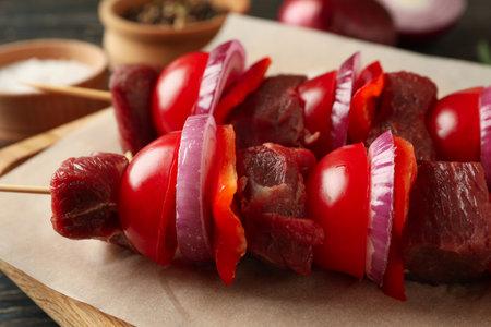 Cutting board with raw shish kebab, close up
