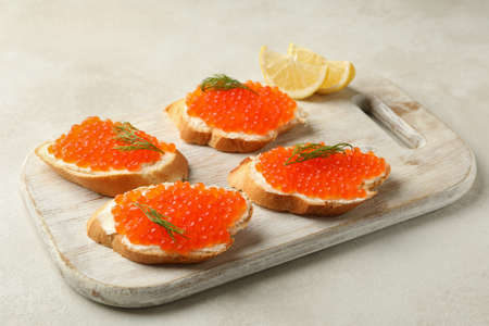 Wooden board with sandwiches with red caviar on white textured background Banco de Imagens