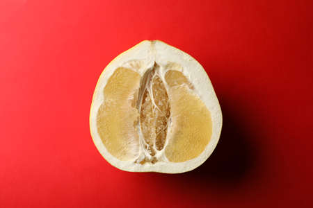 Half of ripe pomelo fruit on red background