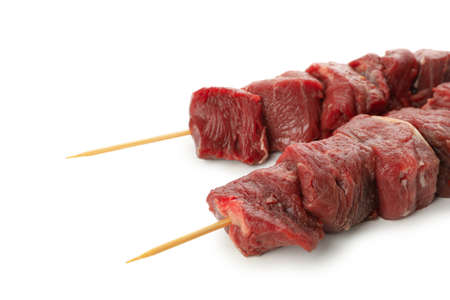 Skewers with raw meat isolated on white background
