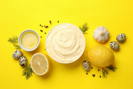 Bowl with mayonnaise and ingredients on yellow background