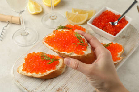 Female hand hold sandwich with red caviar, concept of eating caviar