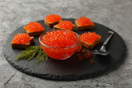 Tray with snacks and bowl with red caviar on gray background
