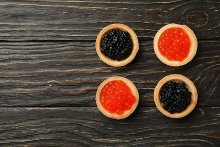 Tartlets with red and black caviar on wooden background, space for text