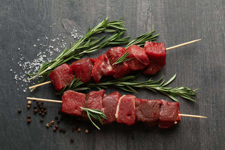 Skewers with raw meat and spices on dark background