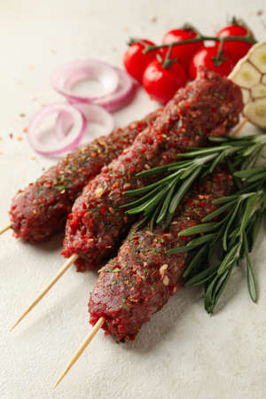 Raw lula kebab, herbs and spices on white textured background