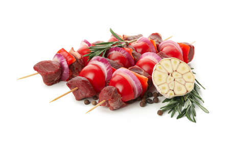 Skewers with raw meat and vegetables isolated on white background