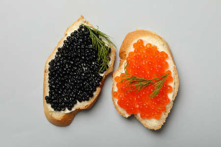 Sandwiches with red and black caviar on gray background, top view