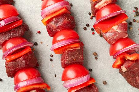 Skewers with raw shish kebab on gray background Banco de Imagens