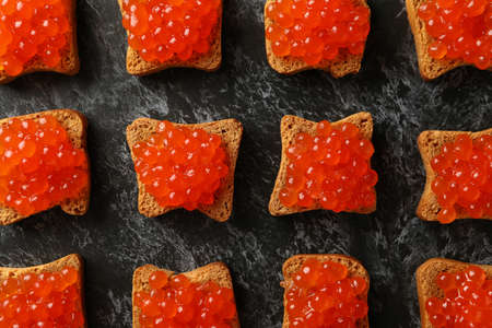 Flat lay with bread slices with caviar on black smokey background