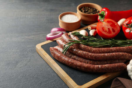 Board with raw sausages, herbs and spices on dark background Banco de Imagens