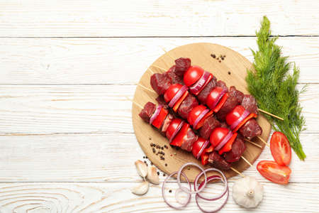Cutting board with shish kebab and ingredients on wooden background Banco de Imagens