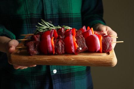 Woman hold board with raw shish kebab, close up Banco de Imagens