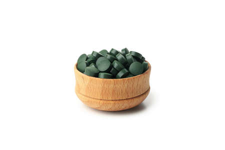Wooden bowl with spirulina pills isolated on white background