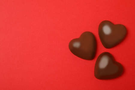 Chocolate hearts on red background, space for text 免版税图像