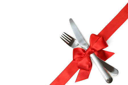 Cutlery with red bow isolated on white background