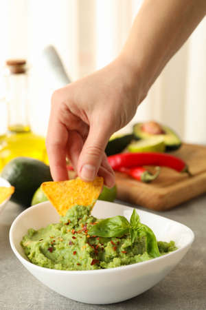 Female hand dips chips slice in guacamole