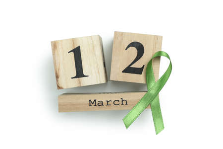 Wooden calendar with 12 march and green awareness ribbon isolated on white background