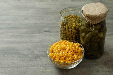 Pickled cucumbers, corn and peas on gray background, space for text