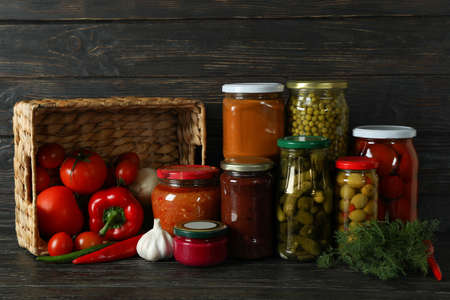 Jars with different canned food on wooden background