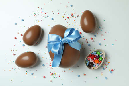 Easter chocolate eggs, candies and sprinkles on white background