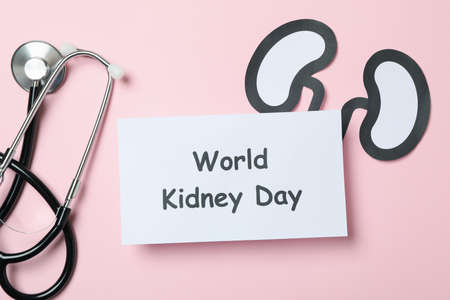 Text World kidney day, paper kidneys and stethoscope on pink background Stock fotó