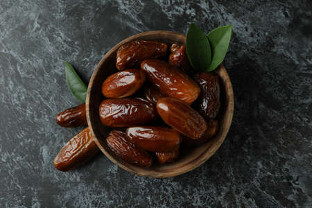 Wooden bowl of dates on black smokey background