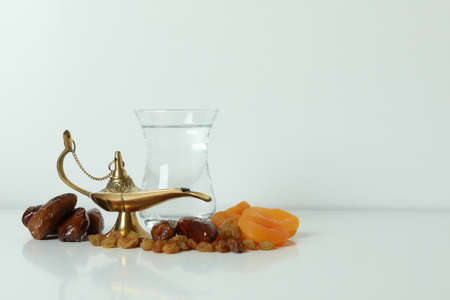 Glass of water, dried fruits and Ramadan lamp on white background