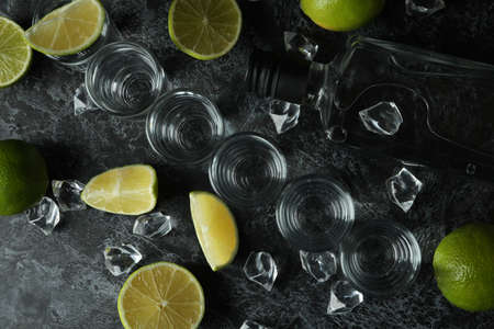 Bottle of vodka, shots, ice cubes and lime slices on black smokey table